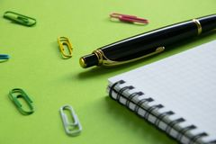 Notepad, paper clips and pen on a green surface Office supplies, Back to school stock photography