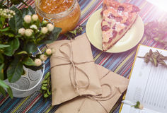Notepad, paper envelope and piece of pie on the colorful tablecloth. Sunlight stock image