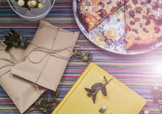 Notepad, paper envelope and piece of pie on the colorful tablecloth. Sunlight stock photos