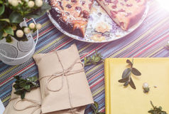 Notepad, paper envelope and piece of pie on the colorful tablecloth. Sunlight stock photo