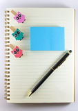 Notepad, paperclip and pen  on white background Royalty Free Stock Image