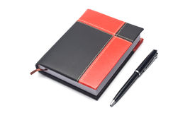 Notepad and pen. Notepad in the red-black cover and pen Royalty Free Stock Image