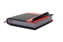 Notepad and pen. Notepad in the red-black cover and pen Royalty Free Stock Photos