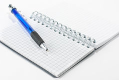Notepad and a pen. A notepad and a pen isolated on a white background Royalty Free Stock Photo
