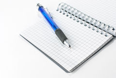 Notepad and a pen. A notepad and a pen isolated on a white background Royalty Free Stock Photos