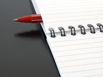 Notepad with pen. Notepad with red pen close-up fragment at the black background Royalty Free Stock Images