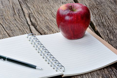 Notepad with pen and apple fruit on table Royalty Free Stock Photo