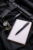 Notepad with pen on black cloth with rifle and compass. Notebook with white pages and pen on black cloth with assault rifle and compass.Top view stock photo