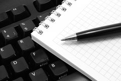 Notepad with pen on a black computer keyboard Stock Images