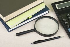 Home savings, budget concept. Notepad, pen, calculator,magnifying glass on wooden office desk table. royalty free stock photography