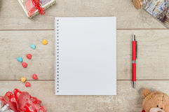 Notepad, pen, candy and teddybear on wooden table Royalty Free Stock Photos