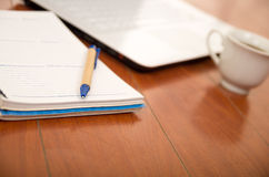 Notepad, pen and coffee cup as seen from above sitting on wooden surface.  stock image