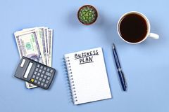 Notepad with pen, coffee, dollars, calculator and cactus on a blue background. Copy the space. Top view. Financial, marketing, bus Royalty Free Stock Image