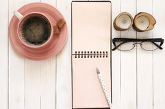 Notepad with pen, coffee, glasses and candles on desk Stock Photos