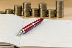Notepad pen and coins. On a light background stock photo