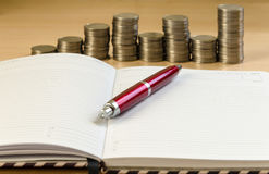 Notepad pen and coins. On a light background royalty free stock image