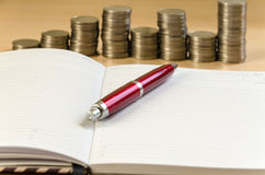 Notepad pen and coins. On a light background royalty free stock photos