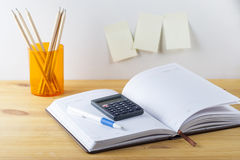 Notepad with pen container with pencils, calculator are on a wooden table. On the wall near the table glued paper for notes. Stock Photography