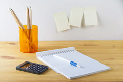 Notepad with pen container with pencils, calculator are on a wooden table. On the wall near the table glued paper for notes. Stock Images