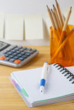 Notepad with pen container with pencils, calculator are on a wooden table. On the wall near the table glued paper for notes. Royalty Free Stock Photos