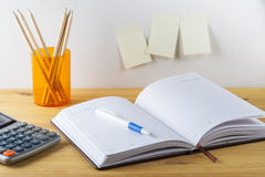 Notepad with pen container with pencils, calculator are on a wooden table. On the wall near the table glued paper for notes. Stock Photos