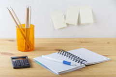 Notepad with pen container with pencils, calculator are on a wooden table. On the wall near the table glued paper for notes. Royalty Free Stock Images