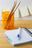 Notepad with pen container with pencils lie on a wooden table. On the wall near the table glued paper for notes. Stock Images