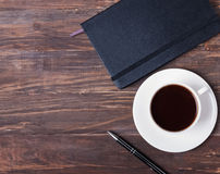 Notepad, pen and cup of black coffee on the wooden table Stock Photo