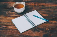 Notepad And Pen. Notepad, pen and cup of hot tea on wooden rustic table royalty free stock photos