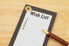 A notepad and pen on a desk with text Wish List and copy-space Stock Photos