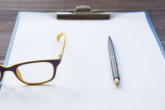 Notepad with pen and eyeglasses Stock Images