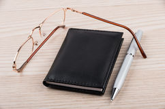 Notepad, pen and glasses on table Stock Image