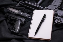 Notepad, pen, gun and knife on black cloth, top view. Notebook for notes with pen and guns with knife on black cloth background stock photos