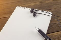 Notepad, pen, headphones on a wooden background education royalty free stock images