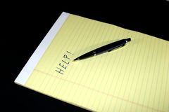 Notepad Pen Help. Yellow notepad with the text HELP and a blue pen Stock Photo