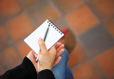 Notepad and pen hold by woman hand Stock Photography