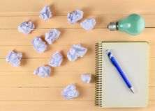 Notepad with a pen, incandescent bulb and crumpled white paper b. Alls on a pink wooden table. Ideological concept, top view royalty free stock image