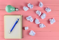 Notepad with a pen, incandescent bulb and crumpled white paper balls on a pink wooden table. Ideological concept, top view. stock photo