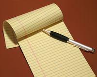 Notepad and pen isolated on a brown background Royalty Free Stock Image