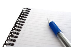 Notepad and Pen on Isolated White. Notepad and pen on a isolated white background at an angle with medium depth of field Stock Photo