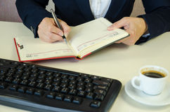 Notepad, pen, keyboard, caffee and hands Stock Photo