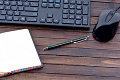 Notepad with pen and keyboard computer on table Royalty Free Stock Image