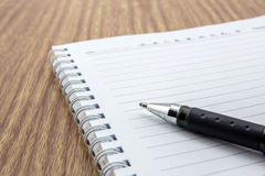 Notepad with pen lying. On the wooden table Stock Photography