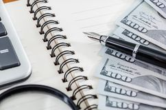 Notepad, pen, magnifier, calculator and dollars royalty free stock images