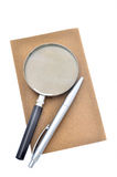 Notepad, pen and magnifying glass isolated Royalty Free Stock Image