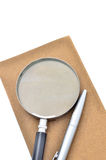 Notepad, pen and magnifying glass isolated Stock Photo