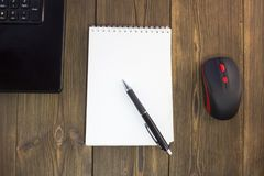 Notepad pen notebook and mouse on a wooden background office royalty free stock image