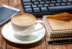 Notepad, pen,phone, envelope, keyboard and coffee cup on a woode Royalty Free Stock Images