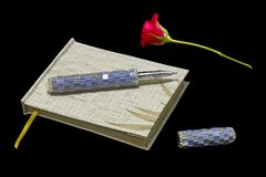 Notepad with pen and red rose. On black background Stock Image
