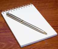 Notepad and pen on table Stock Images